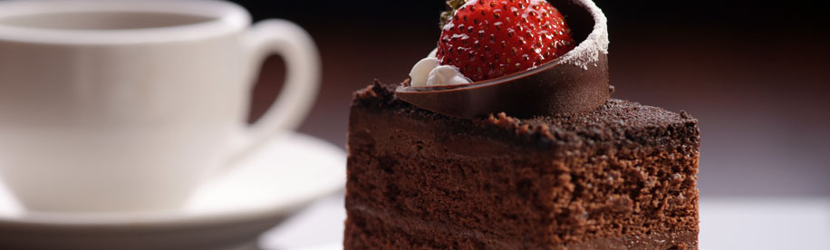 chocolate cake with a strawberry on top and a coffee cup in the background