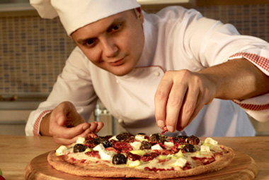 Chef adding toppings to a pizza