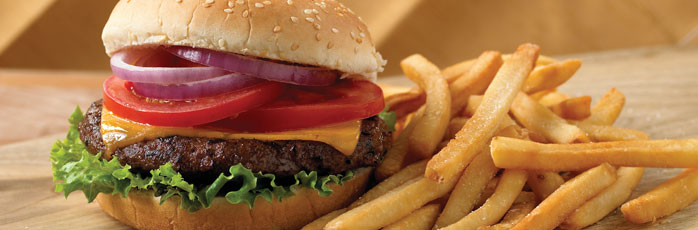 Cheese burger with onions, tomato, and lettuce accompanied by French fries