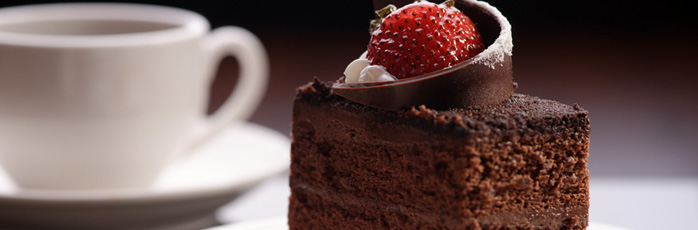 Chocolate cake with a strawberry on top with a coffee cup